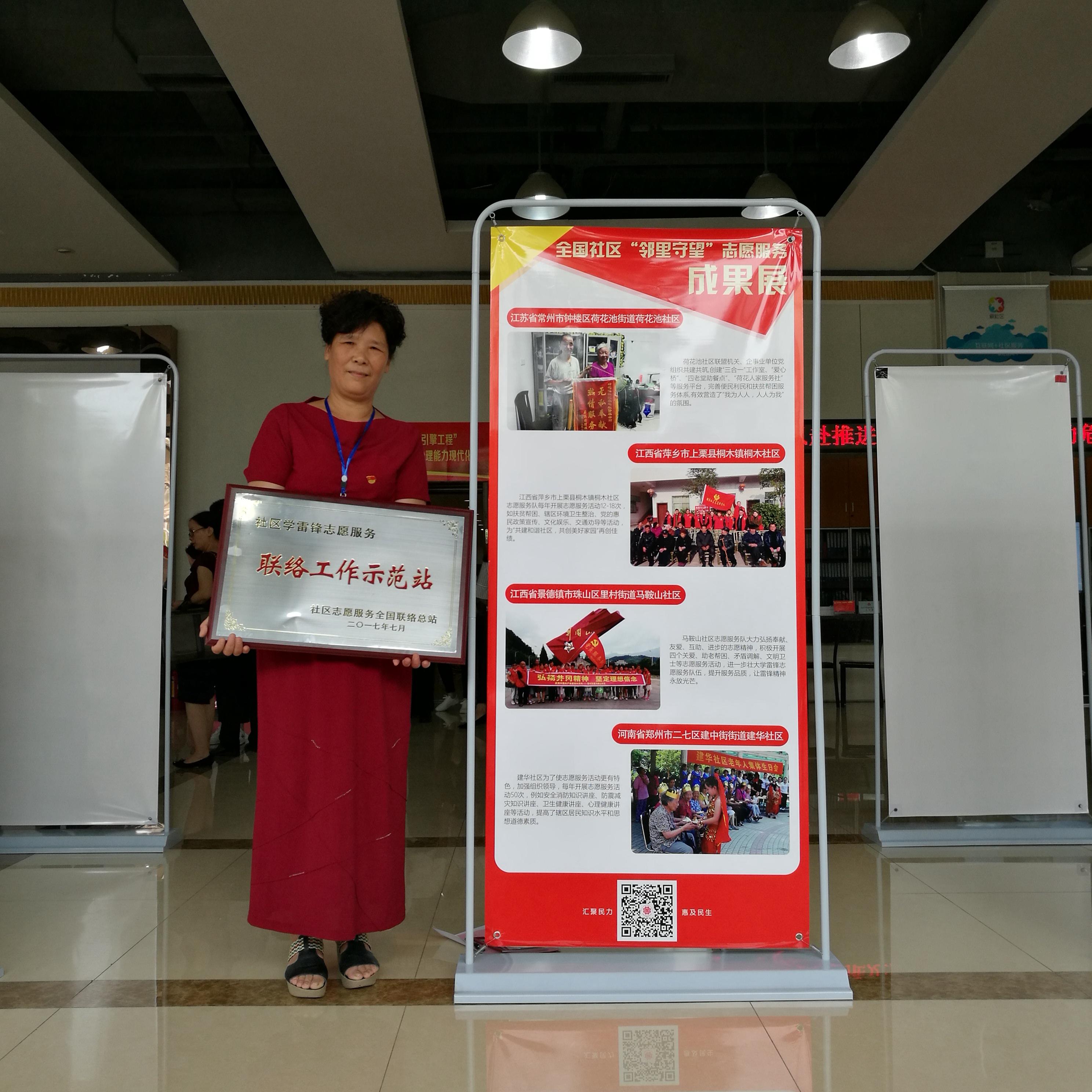 马鞍山社区社区党支部书记、主任齐菊英展示获得的奖牌.jpg
